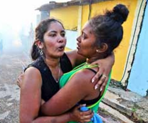 Salimon Jaggernauth left being consoled by a friend on Saturday after her home was destroyed by a fire at Layan Hill, Belmont. Jaggernauth was one of at least six people displaced by the blaze that gutted two homes.
