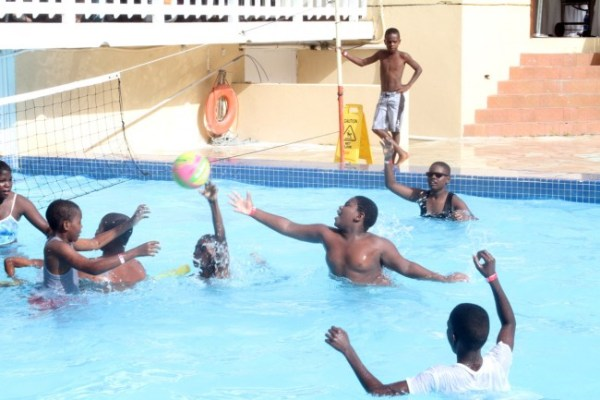 Some young boys enjoying  a game of water volleyball.