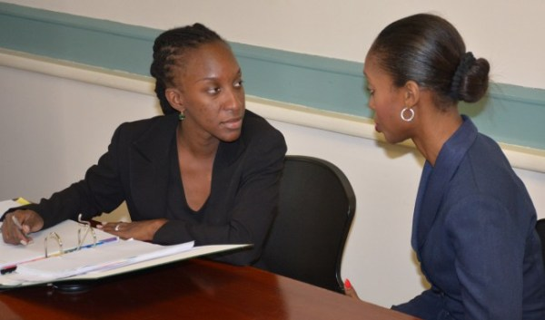 Attorney for Joel Leacock, Jewel Warner (right) having some words with Niketh Smithen of the legal firm Carrington and Sealy, representatives for KPMG.