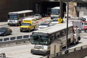 A New Jersey Transit bus (right) being pushed by a tow truck out of the Lincoln Tunnel today in New York as other vehicles use adjacent lanes.