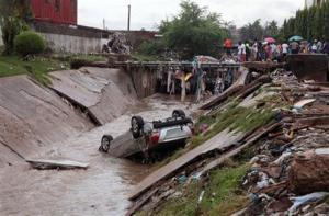 A car lies in a water trench that washed away after heavy rain near a gas station explosion in Accra, Ghana, today.
