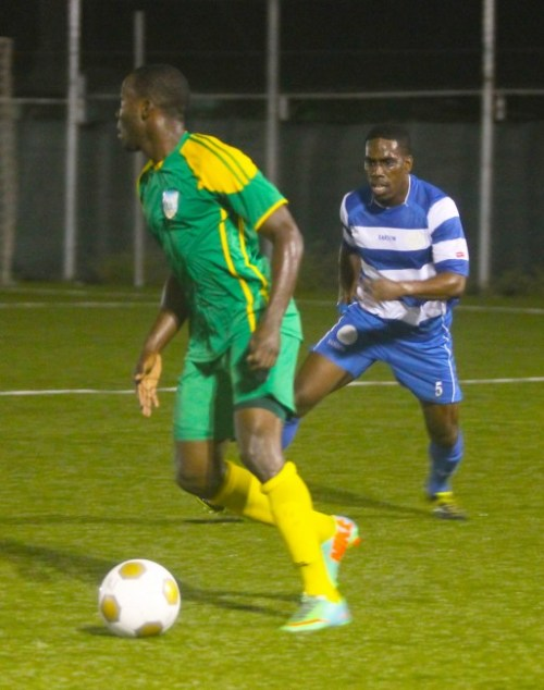 BDFSP's goal scorer Rashad Jules looks to make a pass as Rendezvous defender Romelle Burgess moves in to challenge
