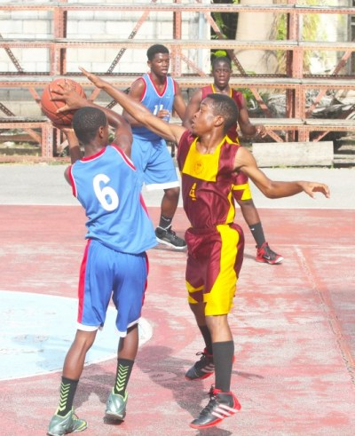 Makaari Jones of Queen's College looks to make a pass but is put under pressure by Raphael Howard of Harrison College.