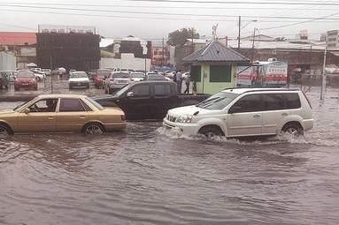 Vehicles passing through floodwaters  at South Quay in Port of Spain.