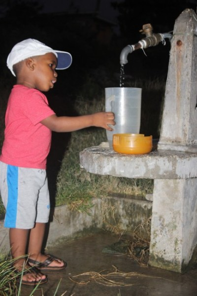 Today this little  one was busy assisting his mother with fetching water.