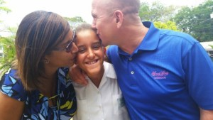 Top three student Zoe Stormes (centre) receiving a kiss from mother Rachel (left) and father Peter.