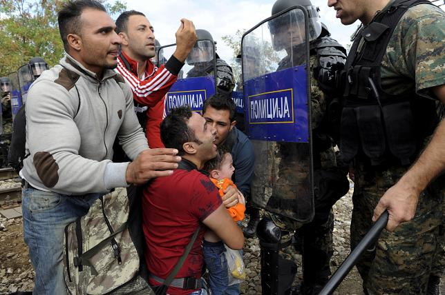 Migrants confronting Macedonian police during clashes at the Greek-Macedonian border, today.