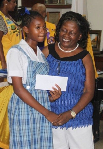 Serina Hinkson shows off her Darcy Cumberbatch Scholarship cheque with, Lorraine Cumberbatch, wife of the late Lion.