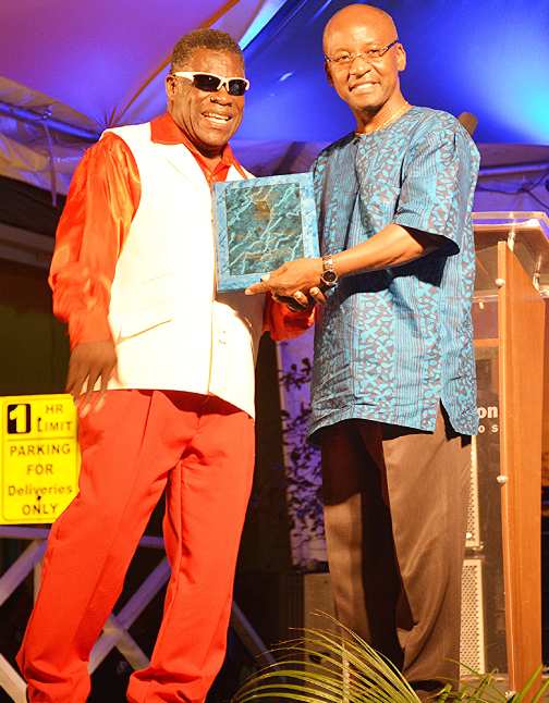 Cassius receiving his Community Independence Celebrations Spouge Award from Minister of Culture Stephen Lashley.