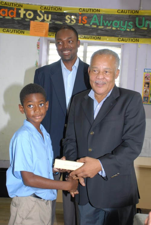 Member of Parliament for St Peter Owen Arthur (at right) presenting pupil Matthew Turton with his tablet, as Barbados Labour Party (BLP) candidate Colin Jordan looks on.