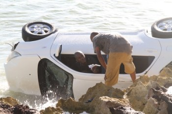 Driver Stephen Arthur being helped out of overturned vehicle. (inset) The Overturned vehicle just off Miami Beach.
