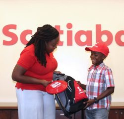 Kiddy Cricket winner Jaden Webster receiving his grant from Scotiabank's Amanda Lynch-Foster.