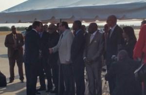 David Cameron greeting officials at the airport.