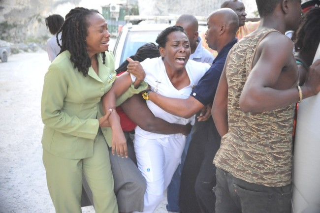 Walcott's sister Tessa Watson being comforted by family members.
