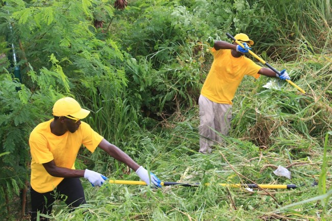 Members of the Adopt-A-KM team cleaning a section of the Highway in the Warrens, St Michael area as they prepare to erect more signs.