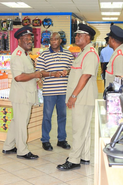 Acting Chief Fire Officer, Errol Maynard, (left) has a word with tenant of Mall 16 on Swan Street, while Deputy Chief Fire Officer, Lloydson Phillips looks on.