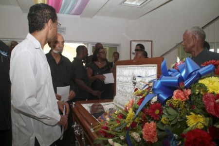 "Pan-Africanists David Comissiong (left), Robert ""Bobby"" Clarke and Muhammad Nassar viewing the body of the late Trevor ""Job"" Clarke."
