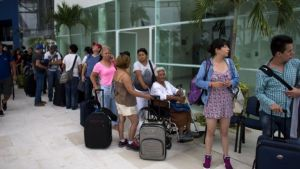 Tourists queuing for buses  in Puerto Vallarta after being told to leave their hotels.
