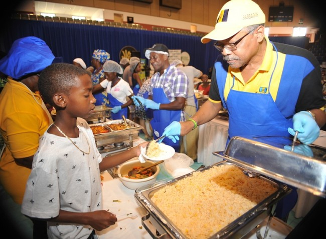 Away from the classroom Principal of Parkinson Secondary Jeff Broomes readily shares this lad some of his split peas and rice with frizzled salt fish – A la Broomer.