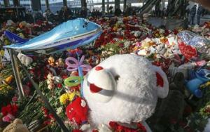 Floral tributes, toys and candles photographed at an entrance of Pulkovo airport during a day of national mourning for the victims of the plane crash, outside St Petersburg, Russia, today.