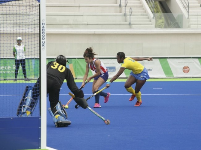 Takirsha Cambridge applying pressure to Paraguay's Andrea Cardozo, while Barbados goalie Sheena Nicholls positions for a save.