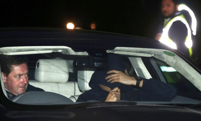 A man believed to be Jose Mourinho covers his face under a hoody as he is is driven out of Chelsea training in Cobham southern England today.