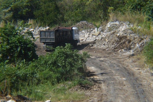 Trucks laden with waste entering and leaving the area.