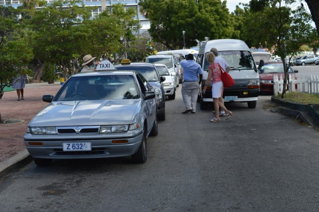 Here two tourists take a taxi while other vehicles remain parked due to the slow period Inset, taxi men on Upper Broad Street.