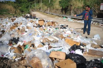 Acting General Manager Rosalind Knight gesturing at a pile of illegally dumped refuse.