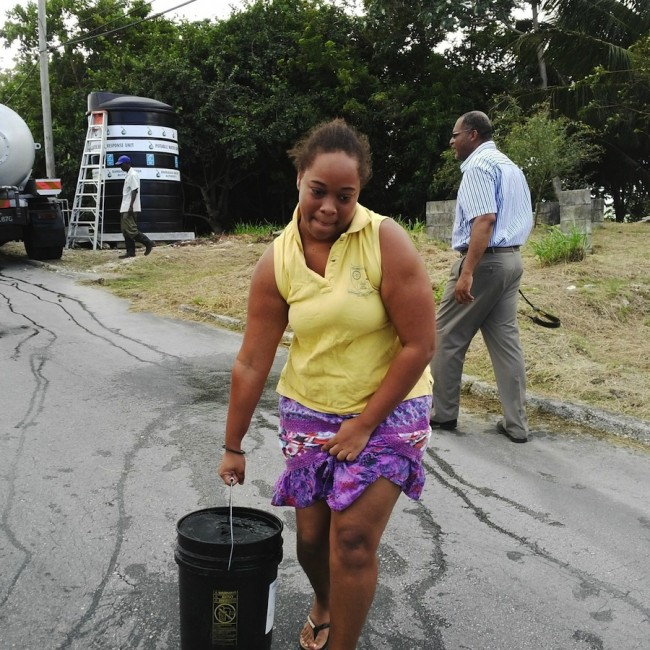 Kerri-Anne Turton of Branch Road, St Joseph, seems to be straining every muscle in her body in carry this bucket of water but could be saying what a relief to finally seeing a BWA water tanker even though it arrived in her district just after 1 p.m. yesterday