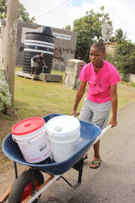A resident leaving the tank located at the Branchbury Community Centre with his cart filled  with buckets of water.