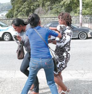 Mother of Keron Warrican (right) fighting with his common law wife Salisha Khan (left) at the St James Forensics Science Centre yesterday.