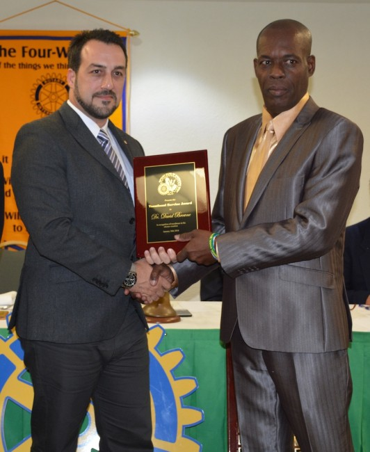 Awardee Dr David Browne (at right) receiving his plaque from Rotary West president Farid Mansoor.