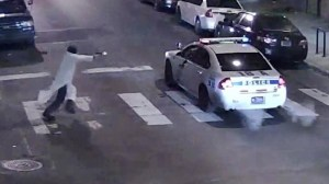 A still image from surveillance video shows a gunman (left) approaching a Philadelphia police vehicle in which Officer Jesse Hartnett was shot shortly before midnight yesterday in Philadelphia, Pennsylvania.