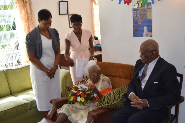 Barbados' newest centenarian Dorothy Casey received a flower basket from Governor General Sir Elliot Belgrave. Looking on is manager of Bromswood Retirement Home Marilyn Sobers (left) and granddaughter Heather Cave.