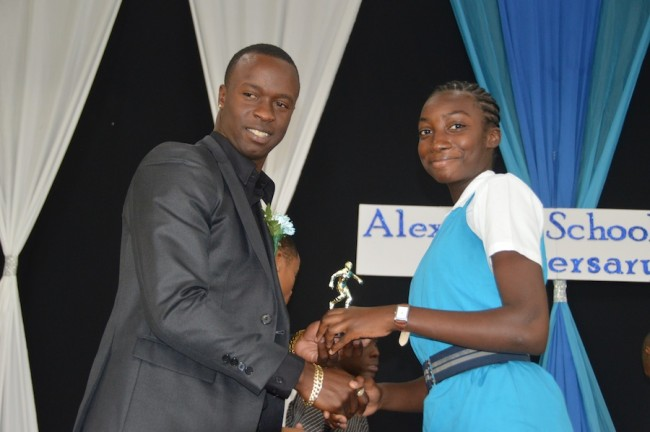 Past student and West Indian fast bowler Kemar Roach presenting  Tia-Briggs Thompson with an award for girls football.