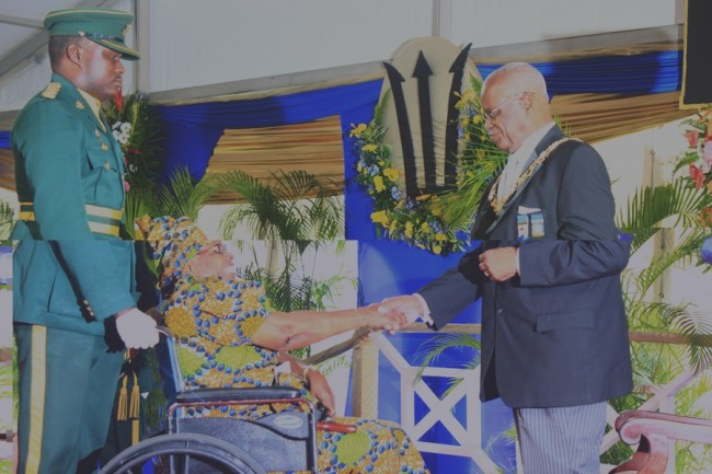 Cynthia Wilson being greeted by Governor General Sir Elliott Belgrave before receiving  her medal.