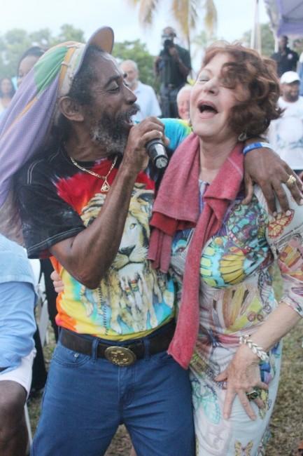 Ras Iley singing with a fan.