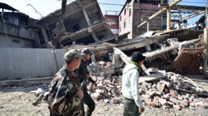 Security personnel walking past a collapsed building in Imphal, India, after a magnitude-6.7 earthquake today.