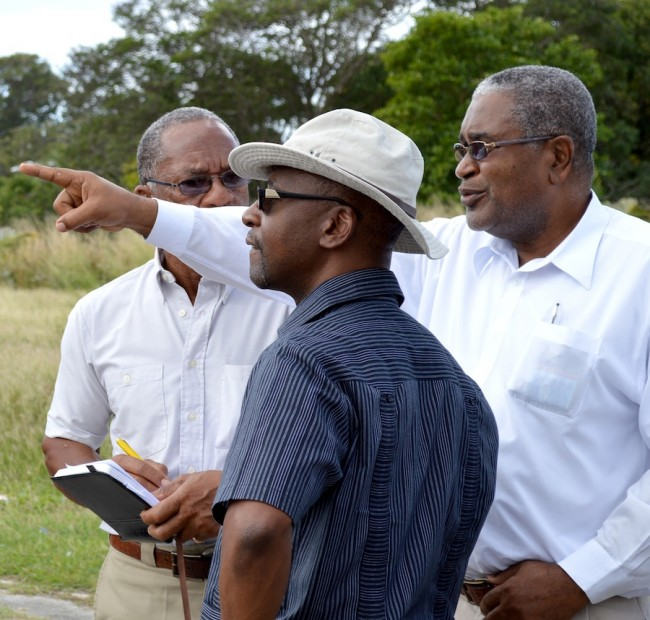 Sports Minister Stephen Lashley listens to senior technical officer at the NSC Ronald Thompson during their visit to the Victor Clarke playing field. Partially obscured is NSC chairman Michael Power.