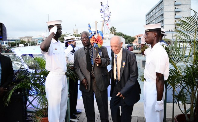The oldest active fisherman Fred Watson (second right) and the oldest active seafarer Albert Broomes (second left) arriving with the commemorative Broken Trident.