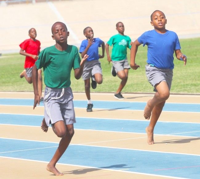 Tyrese Clarke of Green House slammed the field to win the under-13 boys 200m ahead of Shawn Jack of Blue House.