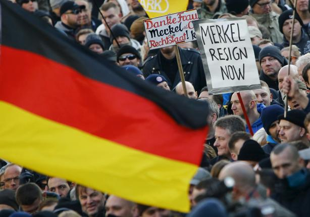 Supporters of anti-immigration right-wing movement PEGIDA (Patriotic Europeans Against the Islamisation of the West) demand the resignation of German Chancellor Angela Merkel on a placard during a demonstration rally in Cologne, Germany. REUTERS/Wolfgang Rattay