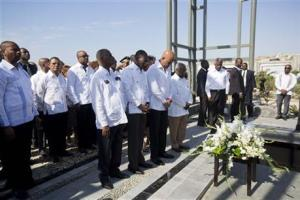 Haiti's President Michel Martelly (second from right centre), Prime Minister Evans Paul (second from left centre) bowing their heads before a floral tribute during  a memorial service marking the sixth anniversary of the 2010 earthquake, north of Port-au-Prince, Haiti, today.