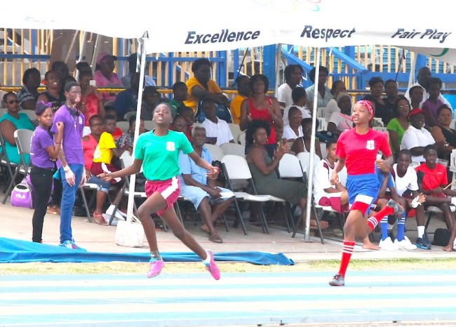 Akeila Lovell of Set D looked relieved after crossing the finish line first in the under-15 girls 200m ahead of Abrianne Bend of Set B.