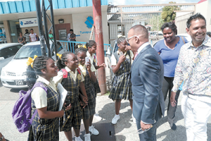 Crime Watch host Ian Alleyne speaks with pupils from the Good Shepherd Anglican Primary School after appearing at the Tunapuna Magistrates' Court yesterday.