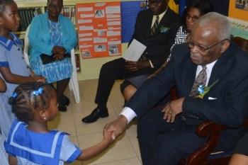 Four-year-old Ajadia Roach shaking Sir Elliott's hand.