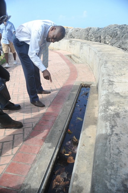 Acting Chief Environmental Officer Desmond King inspecting a section of the Speightstown boardwalk that is filled with dirty water and mosquito larvae (inset).