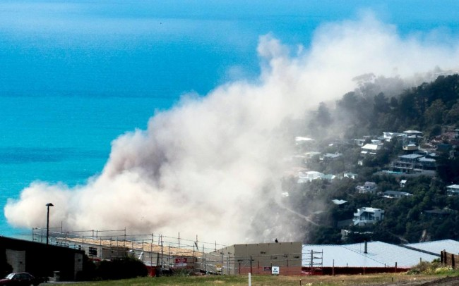 Dust and debris rise above houses after a cliff collapsed due to an earthquake on the Whitewash Head area, located above Scarborough Beach in the suburb of Sumner, Christchurch, New Zealand, February 14, 2016. REUTERS/Richard Loffhagen/Handout via Reuters