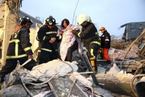 Rescue personnel help a victim at a damaged building after an earthquake in Tainan, southern Taiwan, today.